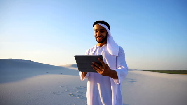 Successful Arabian businessman holds in hands and uses tablet, standing among big desert on summer evening video