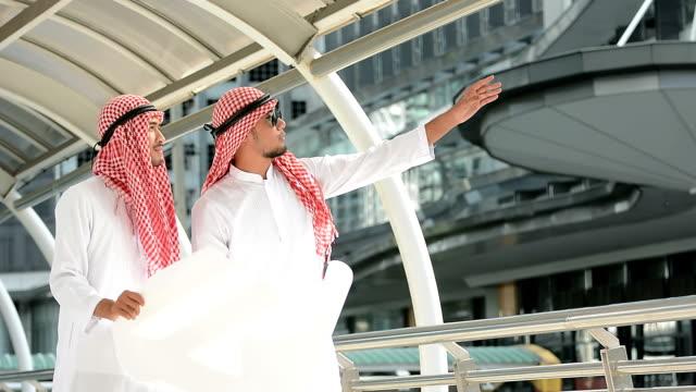 successful arabic businessmen discussing blueprint building project plan on modern city background - arabia saudita video stock e b–roll