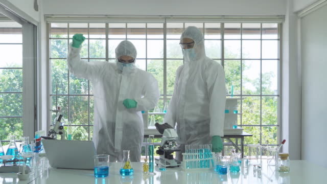 vidéos et rushes de scientifique asiatique réussi travaillant sur le tube à essai bleu pour analyser et développer le vaccin du virus covide-19 en laboratoire dans la technologie médicale, chimie, soins de santé, concept de recherche. expérimental. - 18 19 ans