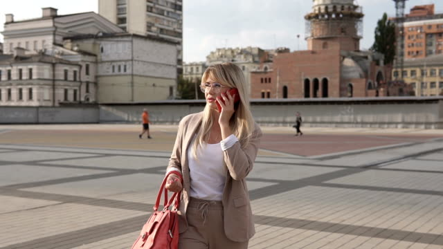 Successful business girl talking on the phone. A girl in a business suit in a big city is in talks on a smartphone. - vídeo
