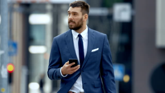 Successful Business Man Uses Smartphone While Walking on the Big City Business District Street.
