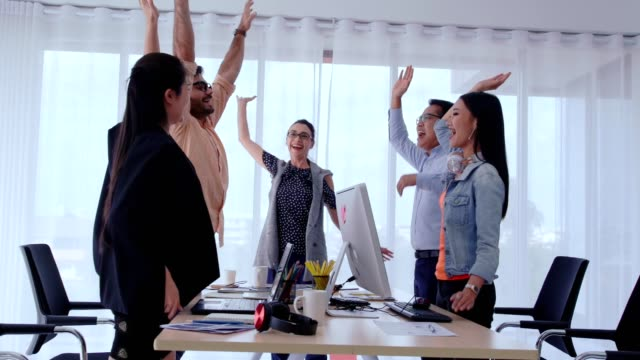 Successful business people celebrating project success at office. Successful business people group celebrating project success at office. Team winner and collaboration achievement concept. employee engagement stock videos & royalty-free footage