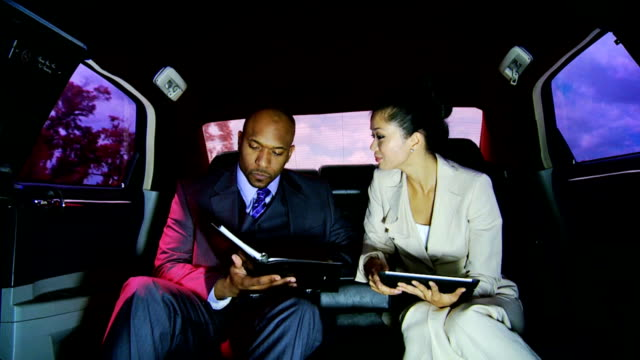 vidéos et rushes de les gens d'affaires réussies voyage de limousine avec chauffeur - book