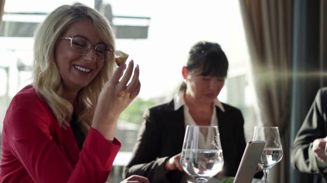 Successful business woman enjoying bruschetti at business lunch with her colleagues Cheerful multiracial group of business people enjoying lunch at luxury restaurant and having a fun time together free stock without watermark stock videos & royalty-free footage