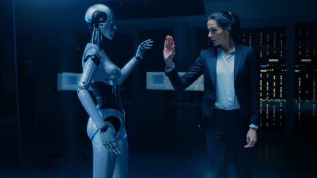 vídeos de stock e filmes b-roll de successful business woman touching hands with robot activating collaboration, teamwork protocol. people and robots working together. artificial intelligence in business - business woman hologram