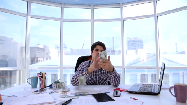 Successful businessman counting and throwing up US dollar money in bright clean office. Business, money, success concept video