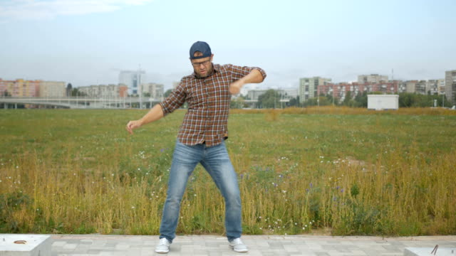 successful businessman dances and rejoices outdoors on the outskirts of new york city. funny man dancing. 4k uhd. - дикая растительность стоковые видео и кадры b-roll