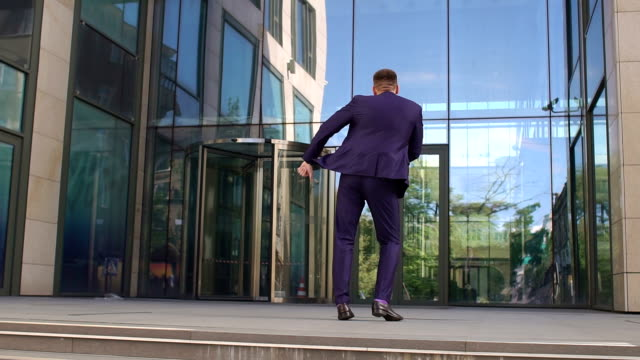 Successful businessman dancing near the building. video