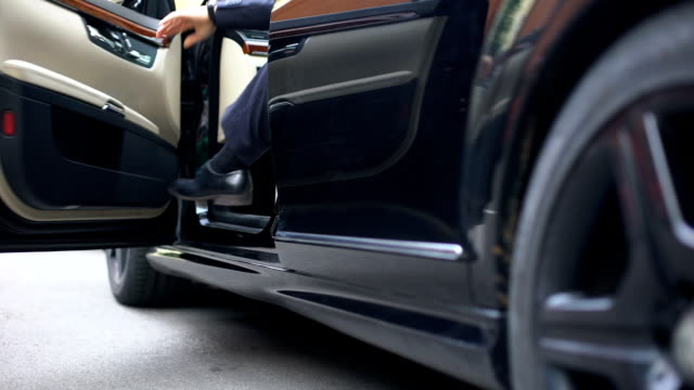 Successful businessman getting out of premium class car, arrival to workplace