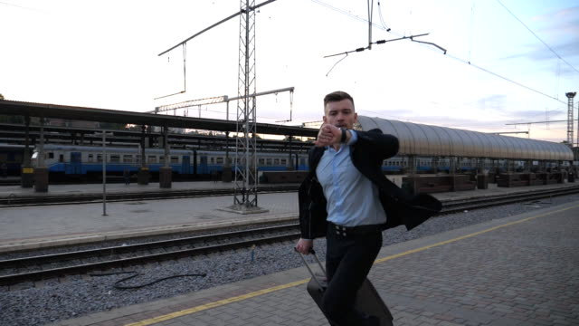 Successful businessman running through railway station and looking at watch. Young man is late for train. Business person jogging with his luggage near railway. Concept of business trip. Slow motion Successful businessman running through railway station and looking at watch. Young man is late for train. Business person jogging with his luggage near railway. Concept of business trip. Slow motion railroad station platform stock videos & royalty-free footage