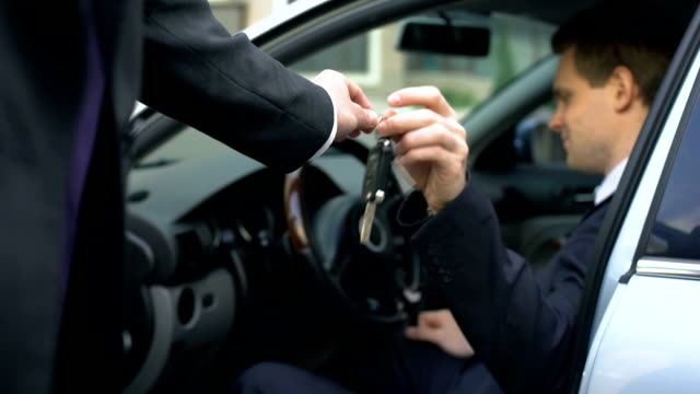 Successful businessman sitting on driver seat, taking keys to car just bought Successful businessman sitting on driver seat, taking keys to car just bought car rental stock videos & royalty-free footage