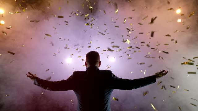 stockvideo's en b-roll-footage met succesvolle zakenman met arms up viert zijn overwinning. het vieren van succes. lage hoek van opgewonden jonge zakenman houden van wapens opgeworpen en uiten positiviteit, terwijl staat op het podium in de achtergrond van de hal - winnen