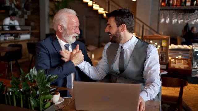 カフェにいる間に合意を結んだ成功したビジネスマン ビデオ