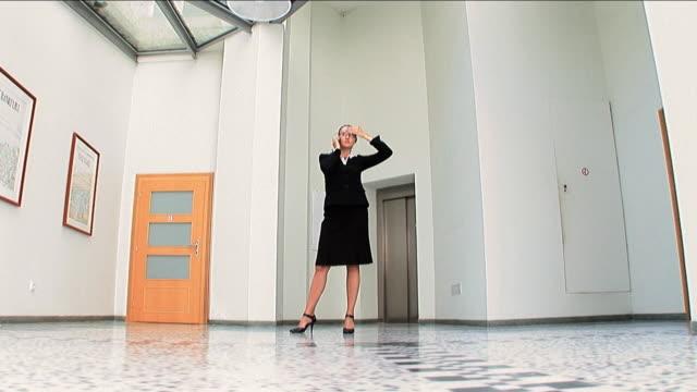 stockvideo's en b-roll-footage met successful businesswoman dealing on the mobile - handen op de heupen