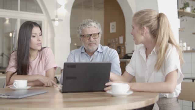 Successful businesswomen showing data via laptop and explaining