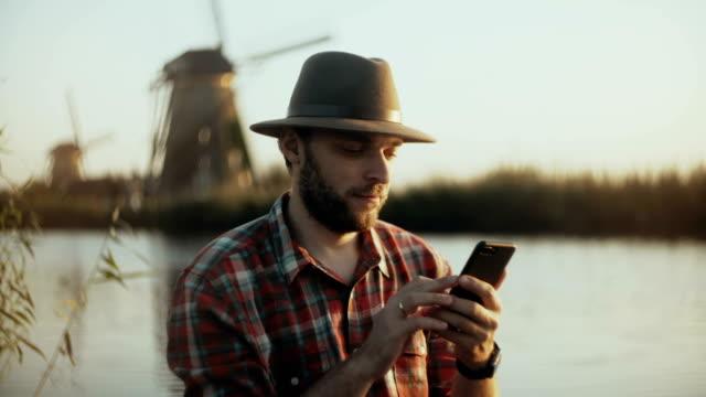 Hombre de éxito caucásico de 4K se encuentra cerca del lago al atardecer. Empresario en un sombrero con smartphone oficina móvil de la bobina de la agricultura - vídeo