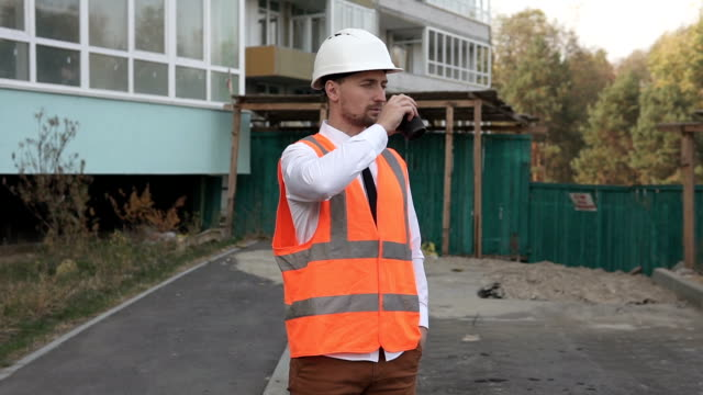 Successful construction worker drinking coffee at a construction site - vídeo