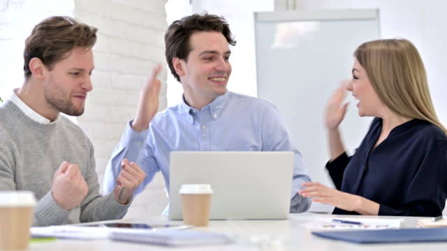 Successful Creative Team doing High-Five in Modern Office