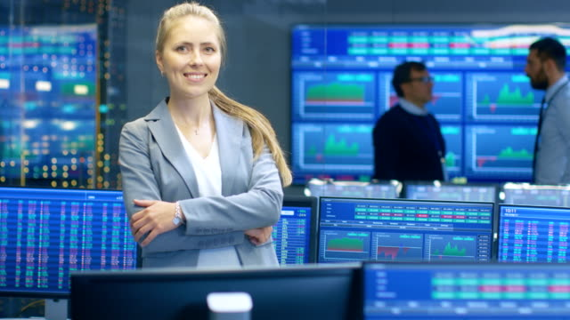Successful Female Stock Trader Crosses Arms and Smiles at the Camera. In the Background Busy Stock Exchange Office with Traders, Brokers and Dealers Selling and Buying Bonds. Displays Show Numbers. video