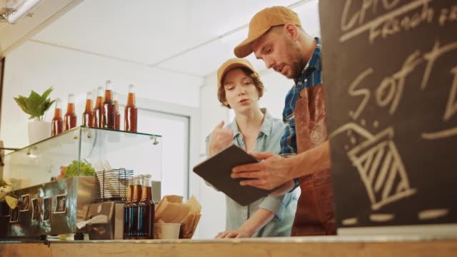 stockvideo's en b-roll-footage met succesvolle food truck man en vrouw medewerkers in brown caps gebruiken een tablet pc. ze bespreken hun winsten en toekomstige bedrijfsplannen. commerciële truck of kiosk verkoopt straatvoedsel en drankjes. - foodtruck