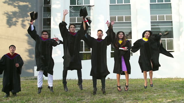 successful graduates in academic dresses are holding diplomas, looking at camera and smiling while jumping for the photo outdoors. - кепка стоковые видео и кадры b-roll