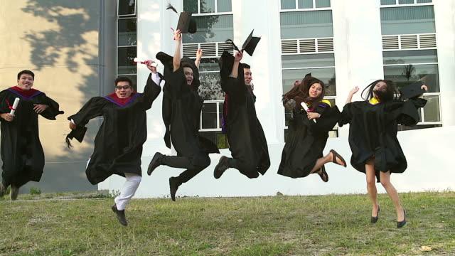 akademik elbiseler başarılı mezunlar diploma holding, kameraya bakıyor ve fotoğraf için açık havada atlama sırasında gülümseyerek. - kep şapka stok videoları ve detay görüntü çekimi