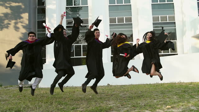 Successful graduates in academic dresses are holding diplomas, looking at camera and smiling while jumping for the photo outdoors.