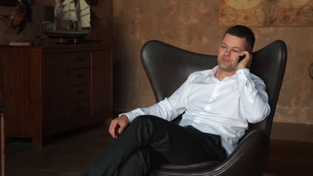 Successful handsome young businessman in a chair talking on the phone Successful handsome young businessman in a chair talking on the phone lounge chair stock videos & royalty-free footage