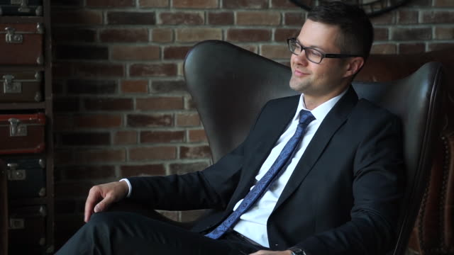 Successful handsome young businessman in armchair Successful handsome young businessman in armchair lounge chair stock videos & royalty-free footage