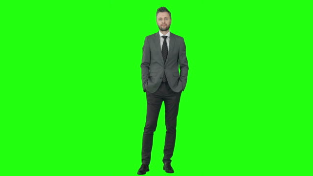 Successful in Business Mid-aged businessman in grey suit walking towards the camera on chroma key background and holding one hand in pocket full length stock videos & royalty-free footage
