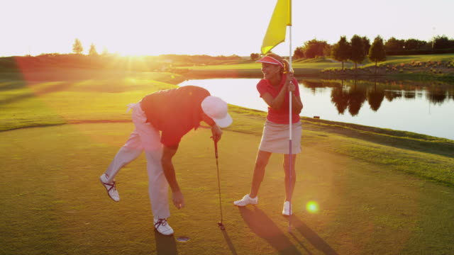 Successful male golfer female caddy winning game sunset video