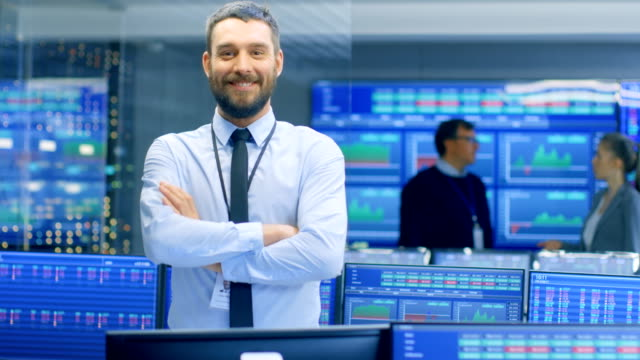 Successful Male Stock Trader Crosses Arms and Smiles at the Camera. In the Background Busy Stock Exchange Office with Traders, Brokers and Dealers Selling and Buying Bonds. Displays Show Numbers. video