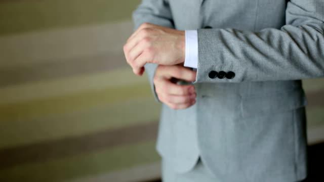 vídeos de stock, filmes e b-roll de bem sucedido homem de terno cinzento endireita as mangas, close-up. - punho