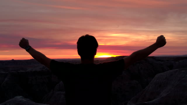 successful man standing on mountaintop at sunset, raising arms towards red sky - avvicinarsi video stock e b–roll