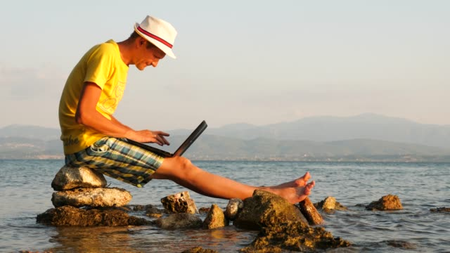 Successful man surrounded by the sea. He works for himself, combines work and rest. Business is booming. Young man looking at the horizon on the sea. Male with laptop satisfied with his work. Greece, Europe, greek island