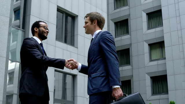 Successful managers handshaking near office building, cooperation, friendship video