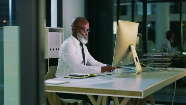 Successful men often have incredibly high work ethics 4k video footage of a handsome mature businessman working on a computer inside his office at night one man only stock videos & royalty-free footage
