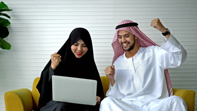 Successful Middle Eastern Male And Female Using A Laptop Computer Working At Home