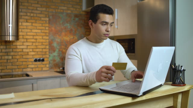 successful mixed race male typing gold card number on laptop, online banking app - credit card filmów i materiałów b-roll