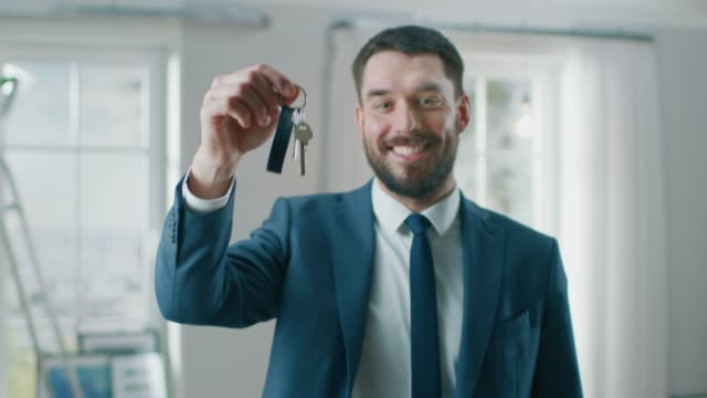 successful real estate agent in a suit smiles and offers keys from a new apartment. standing in the middle of the room that being renovated. spacious new house for sale by professional real estate broker. - key ring stock videos & royalty-free footage