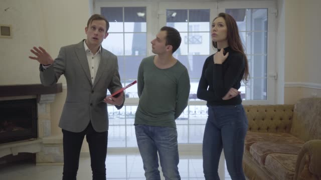 Successful real estate agent shows young confident cute married couple a new home.
