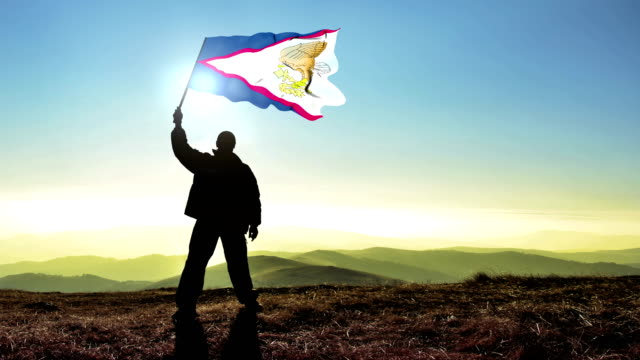 Successful silhouette man winner waving American Samoaman flag on top of the mountain peak. Cinemagraph LOOP background
