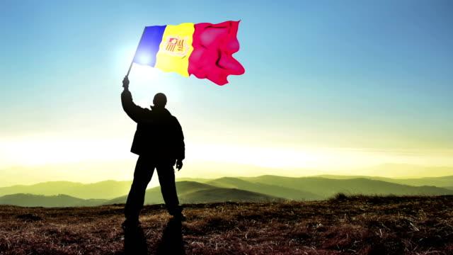 Successful silhouette man winner waving Andorra flag on top of the mountain peak. Cinemagraph LOOP background