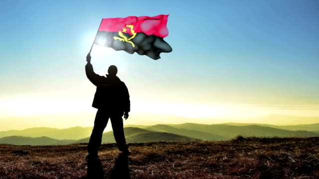 Successful silhouette man winner waving Angola flag on top of the mountain peak, 4k cinemagraph video