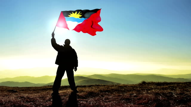 Successful silhouette man winner waving Antigua and Barbuda flag on top of the mountain peak. Cinemagraph LOOP background
