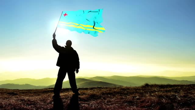 Successful silhouette man winner waving Aruba flag on top of the mountain peak. Cinemagraph LOOP background