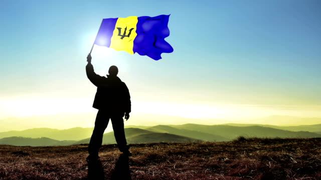 Successful silhouette man winner waving Barbados flag on top of the mountain peak. Cinemagraph LOOP background video