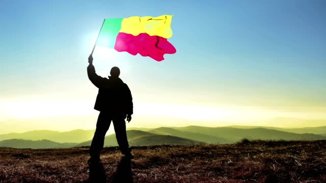 Successful silhouette man winner waving Benin flag on top of the mountain peak. Cinemagraph LOOP background