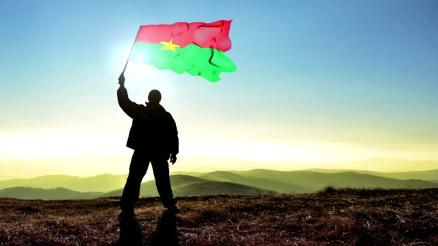 Successful silhouette man winner waving Burkina Faso flag on top of the mountain peak. Cinemagraph LOOP background
