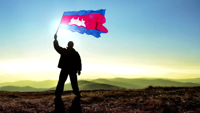 Successful silhouette man winner waving Cambodia flag on top of the mountain peak Cinemagraph LOOP background